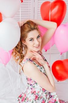 Mädchen im romantischen kleid mit ballonen in form eines herzens