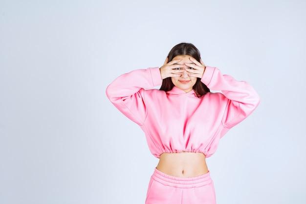 Mädchen im rosa pijamas, das durch ihre finger schaut