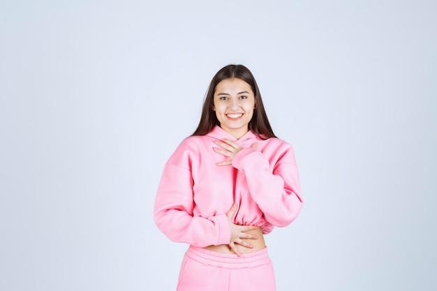 Mädchen im rosa pyjama, das böse und fröhliche posen gibt