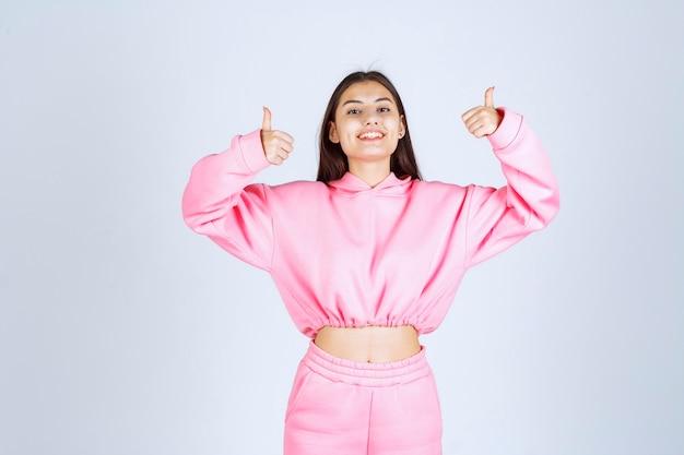 Mädchen im rosa pyjama, das daumen oben zeigt