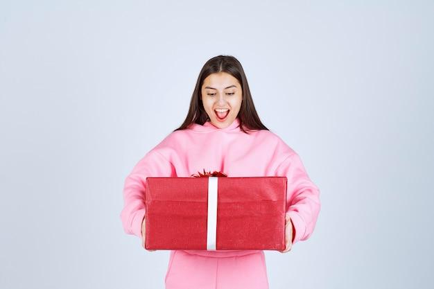 Mädchen im rosa pyjama, das eine große rote geschenkbox umarmt und lächelt.