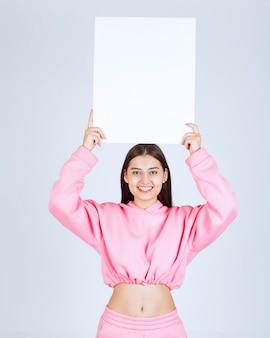 Mädchen im rosa pyjama, das eine leere quadratische präsentationstafel über ihrem kopf hält, damit jeder es sieht.