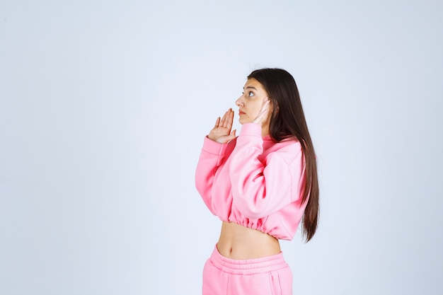 Mädchen im rosa pyjama, das etwas stoppt