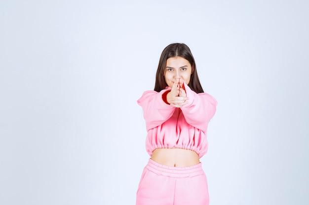 Mädchen im rosa pyjama, das gewehrzeichen in der hand zeigt