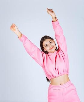 Mädchen im rosa pyjama, das glückliche und verführerische posen gibt