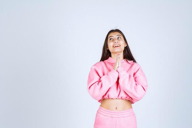 Mädchen im rosa pyjama, das ihre hände vereinigt und betet