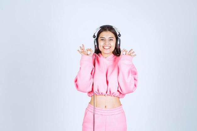 Mädchen im rosa pyjama, das kopfhörer trägt und genusszeichen zeigt. hochwertiges foto