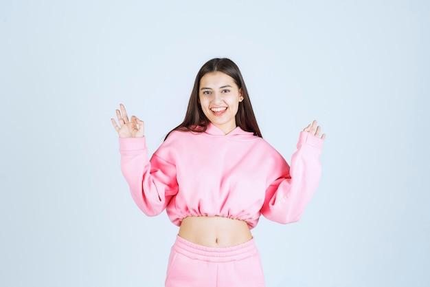 Mädchen im rosa pyjama, das lächelt und etwas genießt.