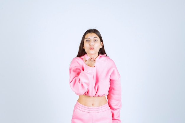 Mädchen im rosa pyjama, das liebe bläst