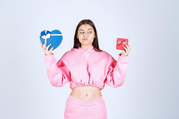 Mädchen im rosa pyjama, das rote und blaue herzform-geschenkboxen hält und wahl zwischen ihnen macht.