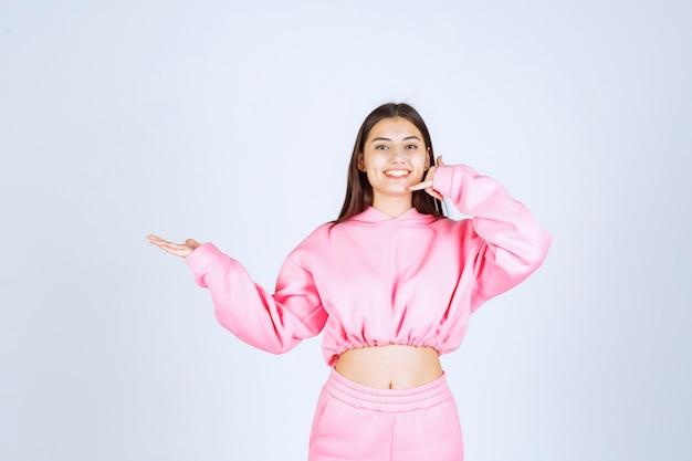 Mädchen im rosa pyjama, das rufzeichen macht