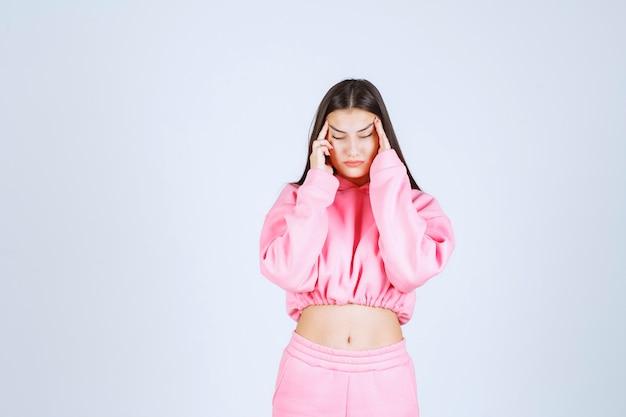 Mädchen im rosa pyjama, das sehr aggressives und wütendes gesicht macht