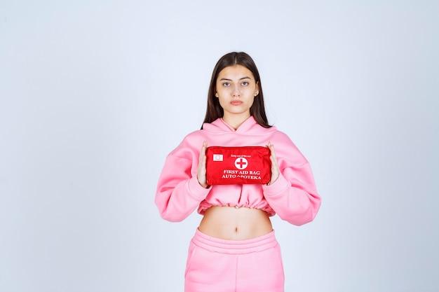 Mädchen im rosa pyjama, der ein rotes erste-hilfe-set hält und es fördert.