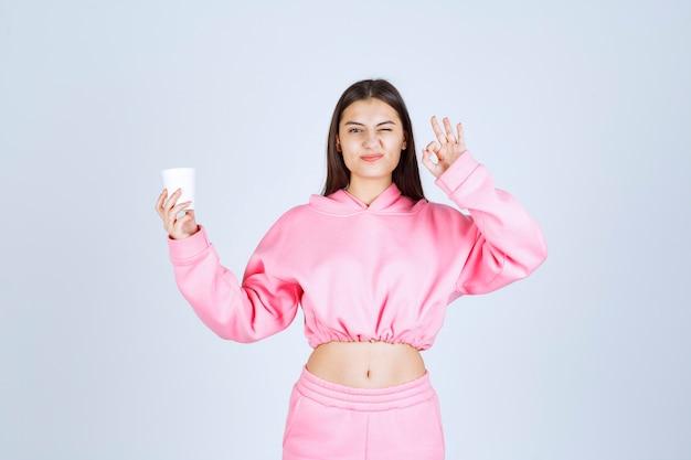 Mädchen im rosa pyjama, der eine kaffeetasse hält und den geschmack genießt