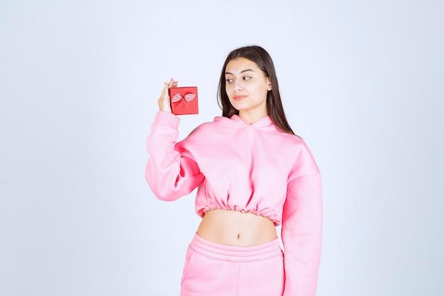 Mädchen im rosa pyjama, der eine kleine rote geschenkbox hält.