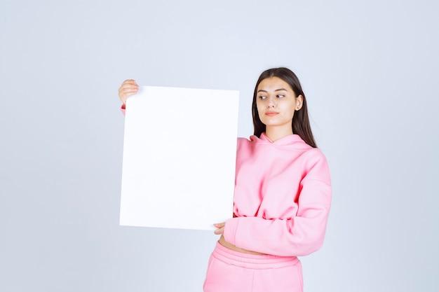 Mädchen im rosa pyjama, der eine leere quadratische präsentationstafel eines neuen projekts hält.