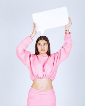 Mädchen im rosa pyjama, der eine leere rechteckige ideentafel hält und unzufrieden aussieht.