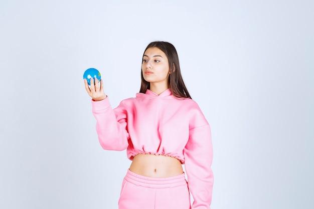 Mädchen im rosa pyjama, der einen mini-globus hält und denkt.
