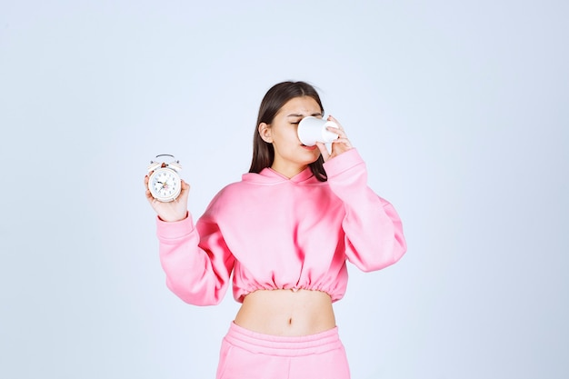 Mädchen im rosa pyjama, der einen wecker hält und eine tasse kaffee trinkt.