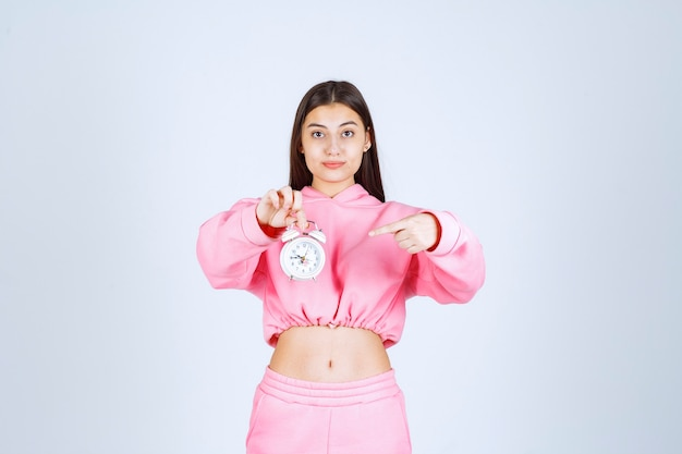Mädchen im rosa pyjama, der einen wecker hält und ihn als produkt bewirbt.