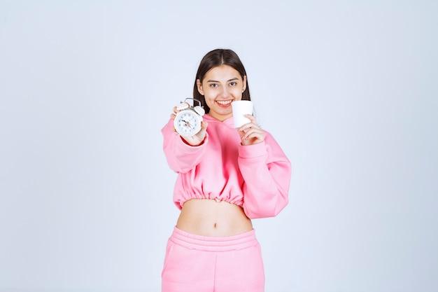 Mädchen im rosa pyjama, der einen wecker und eine tasse kaffee hält.