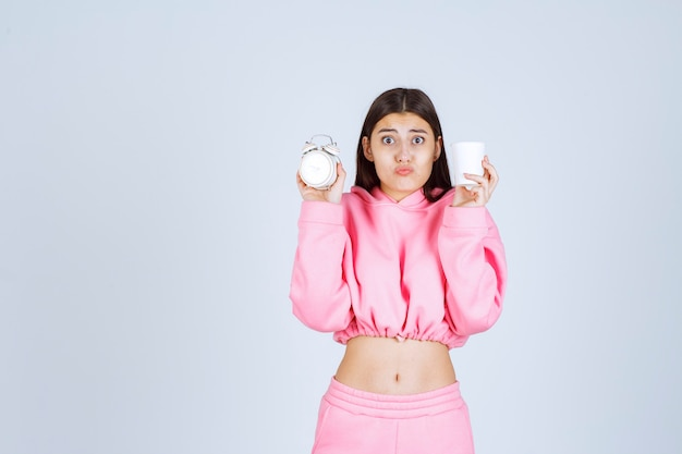 Mädchen im rosa pyjama, der einen wecker und eine tasse kaffee mit einem müden gesicht hält.