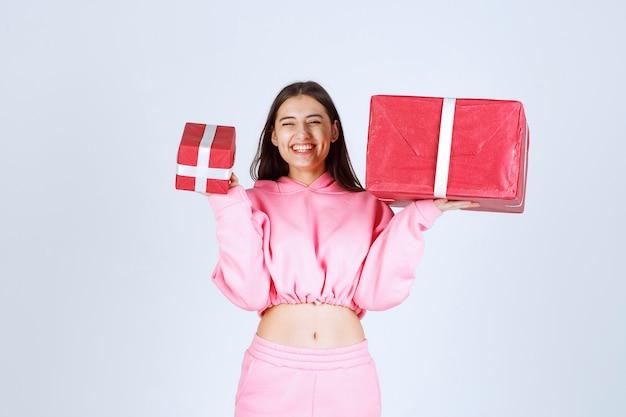 Mädchen im rosa pyjama, der große und kleine rote geschenkboxen hält und lächelt.