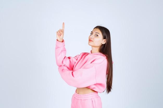 Mädchen im rosa pyjama, der nach oben mit emotionalem gesicht zeigt