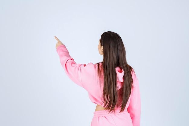 Mädchen im rosa pyjama, der rückwärts zeigt