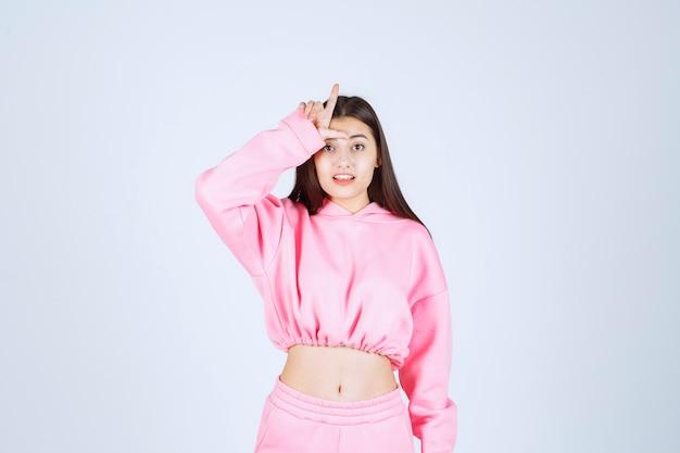 Mädchen im rosa pyjama, der verliererzeichen zeigt