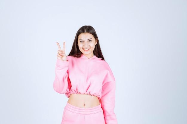 Mädchen im rosa pyjama fühlt sich glücklich und zeigt positives handzeichen.