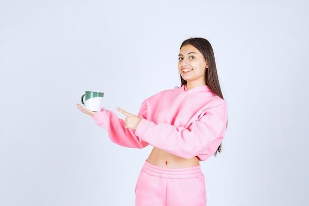 Mädchen im rosa pyjama hält eine kaffeetasse und fühlt sich glücklich.