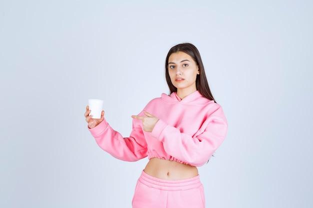 Mädchen im rosa pyjama hält eine kaffeetasse und zeigt auf etwas