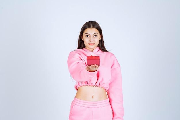 Mädchen im rosa pyjama hält eine kleine rote geschenkbox und bietet sie ihrem freund an.