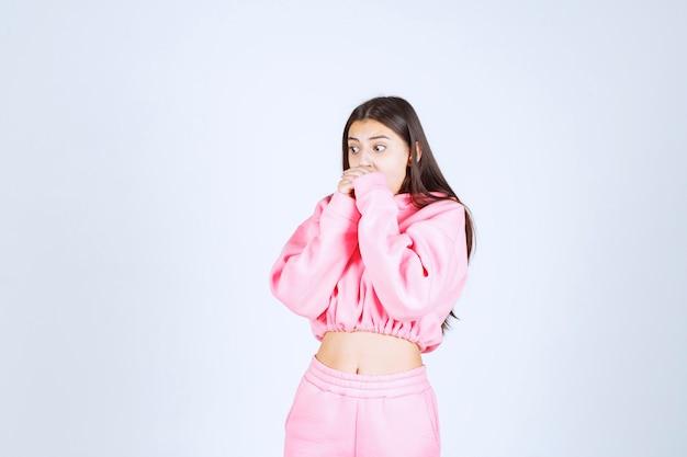 Mädchen im rosa pyjama sieht schockiert und verängstigt aus