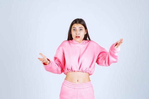 Mädchen im rosa pyjama sieht verwirrt und zweifelhaft aus