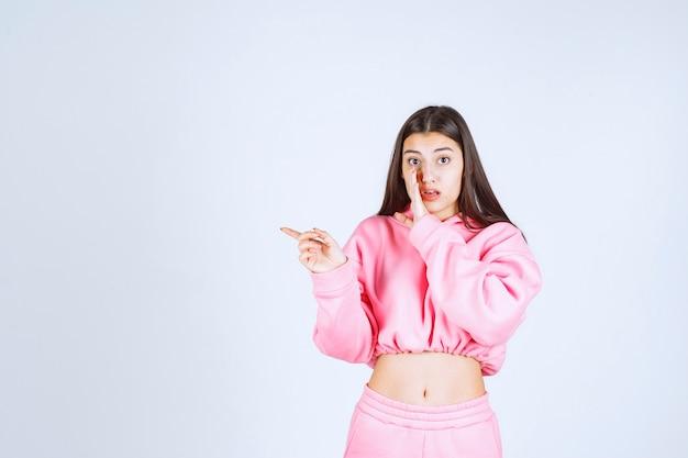 Mädchen im rosa pyjama zeigt auf die linke seite
