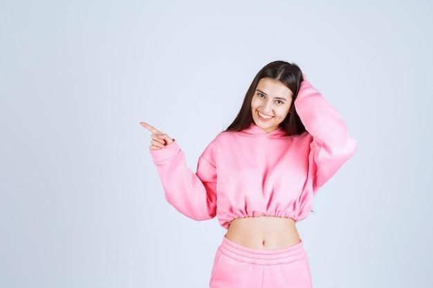 Mädchen im rosa pyjama zeigt auf etwas auf der linken seite