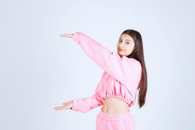 Mädchen im rosa pyjama zeigt die größe eines objekts