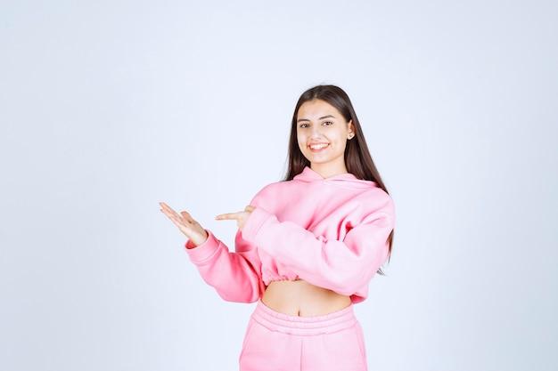 Mädchen im rosa pyjama zeigt etwas in ihrer hand
