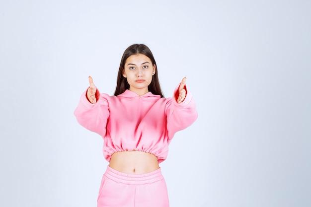 Mädchen im rosa pyjama zeigt nach vorne
