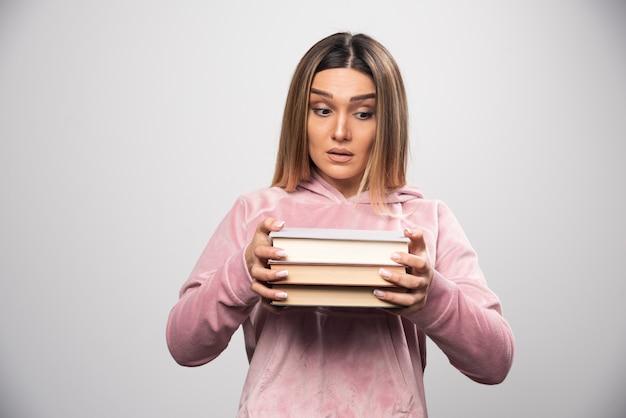 Mädchen im rosa swaetshirt, das schweren stapel bücher hält und trägt.