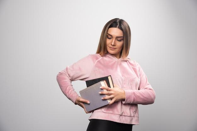 Mädchen im rosa swaetshirt, das schweren stapel bücher hält und trägt