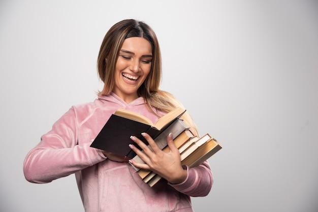 Mädchen im rosa swaetshirt hält einen vorrat an büchern, öffnet einen oben und liest ihn.