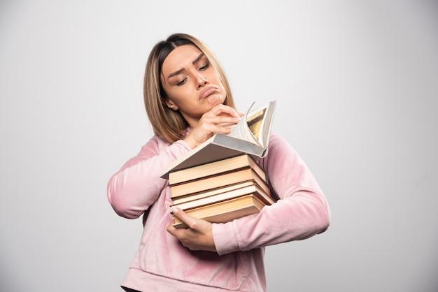 Mädchen im rosa swaetshirt hält einen vorrat an büchern, öffnet einen oben und liest ihn