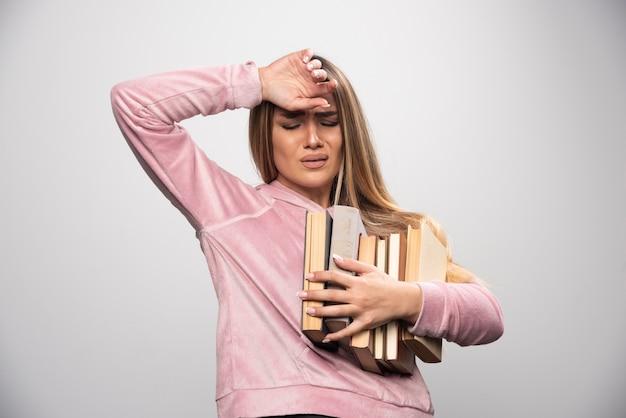 Mädchen im rosa swaetshirt hält einen vorrat an büchern und fühlt sich müde.