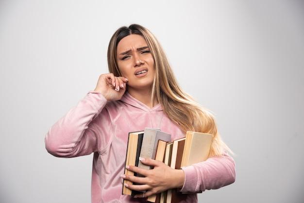 Mädchen im rosa swaetshirt hält einen vorrat an büchern und fühlt sich müde