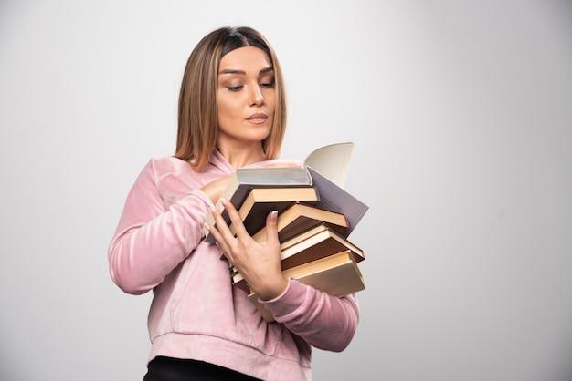 Mädchen im rosa sweatshirt hält einen vorrat an büchern, öffnet einen oben und liest ihn.