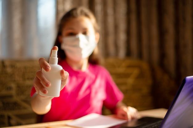 Mädchen im rosa t-shirt, das händedesinfektionsmittel sprüht, während sie an einem laptop arbeitet und zu hause während der coronavirus-quarantäne studiert