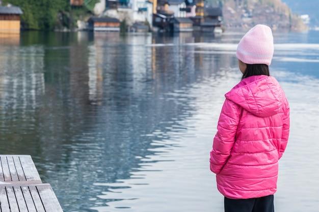 Mädchen im rosa winterstoff, der allein durch einen see steht